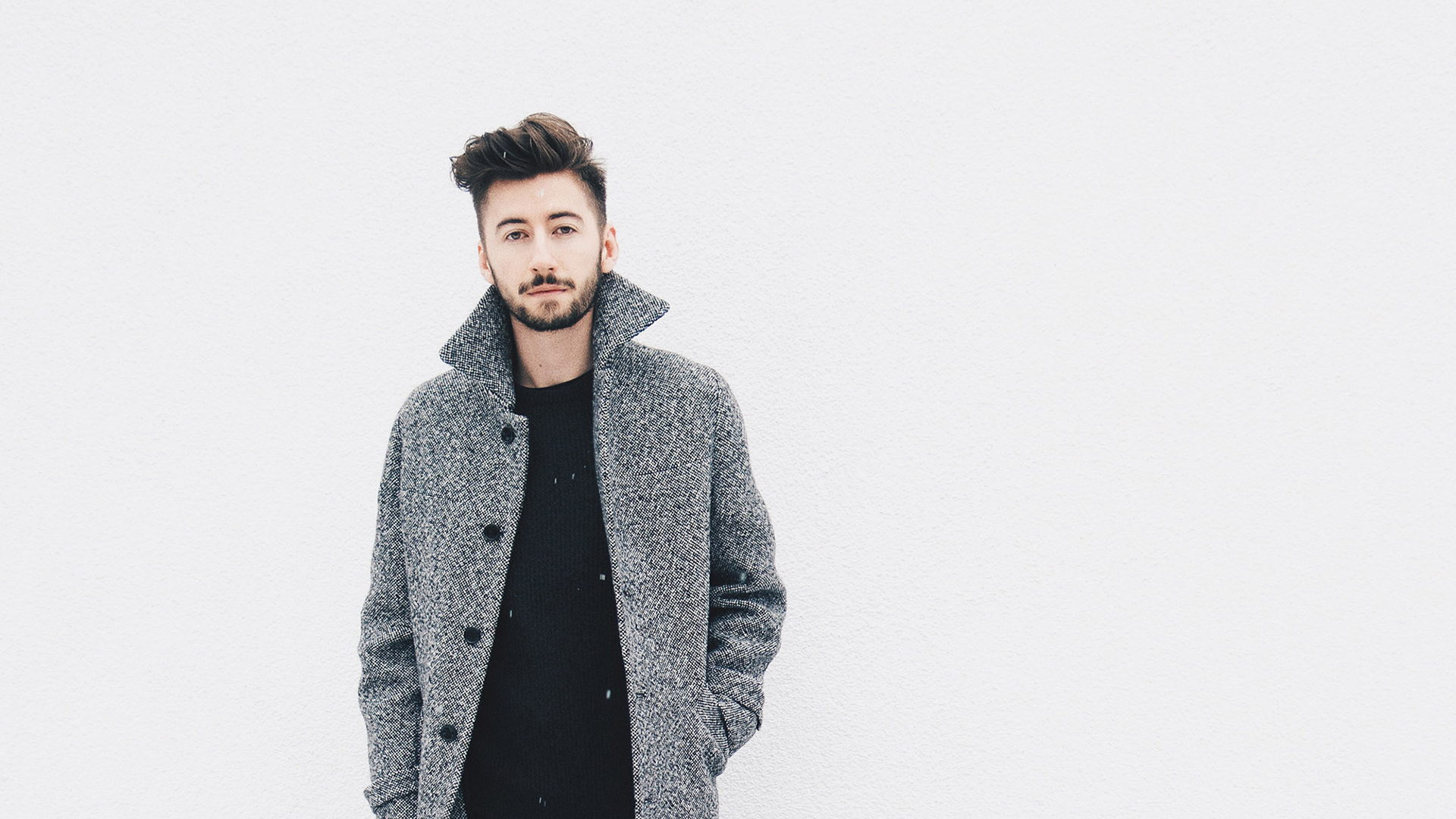 Guy standing in front of white wall with a grey coat on
